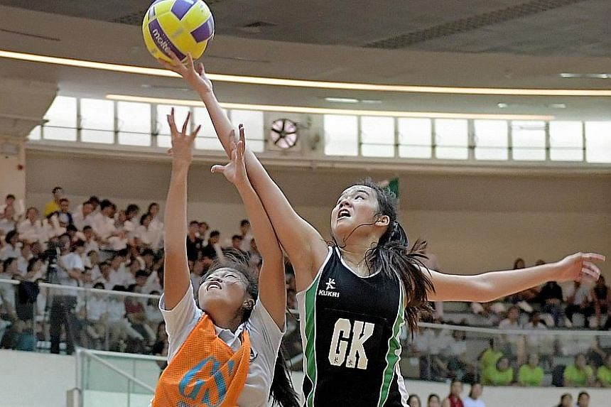 RI goal-keeper (GK) Jamie Lim getting the better of her opponent during the Schools National A Division final against ACJC yesterday. RI won the match 55-32.