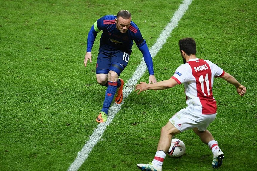 Manchester United captain Wayne Rooney in action against Amin Younes of Dutch side Ajax during the Europa League final on Wednesday. United won 2-0 to secure their third title of the season, after also winning English football's Community Shield and