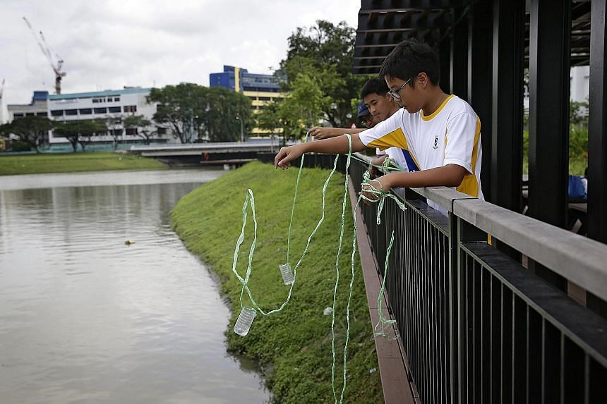 Secondary 1 students Adbeel Yeo (far right) and Cruz Chan (second from right), both 12, from St Andrew's Secondary School collecting water from the Kallang River to analyse its acidity and dissolved oxygen levels. The sample Cruz drew had a surprisin