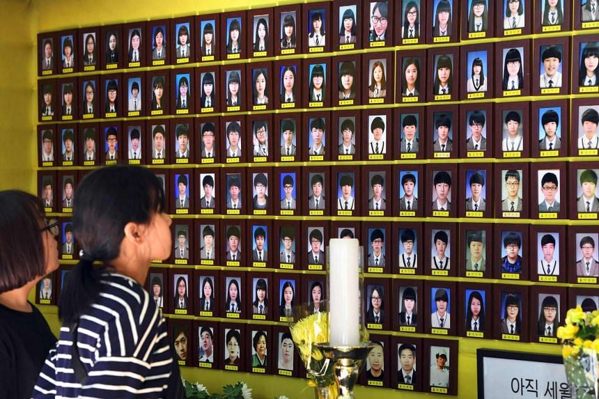 Visitors pray in front of portraits of victims of the 2014 South Korea's Sewol ferry disaster at a memorial altar in Seoul on May 25, 2017.