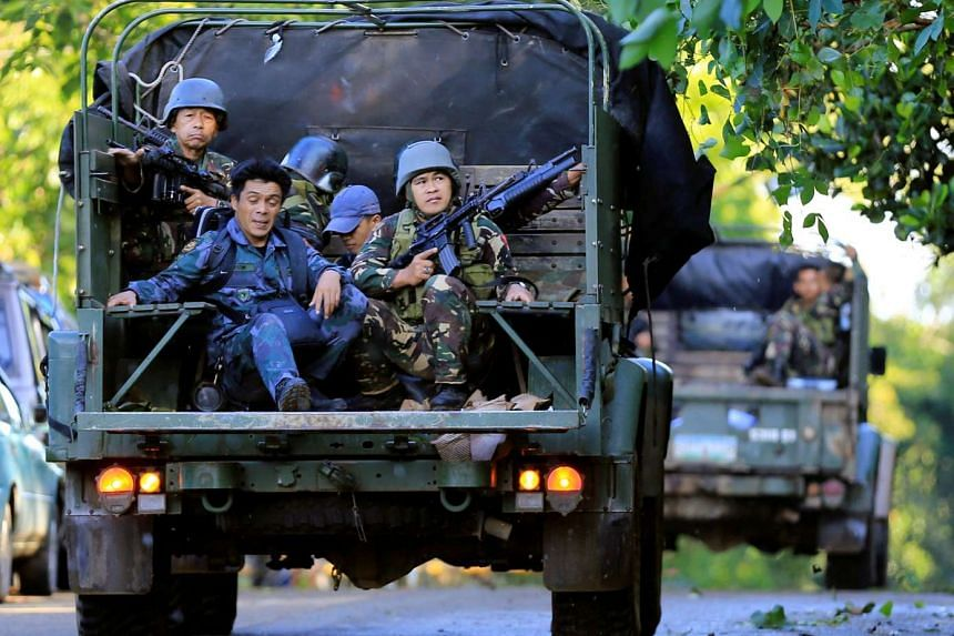 Government soldiers on military vehicles patrol after a continued assault on fighters from the Maute group who have taken over large parts of Marawi city.