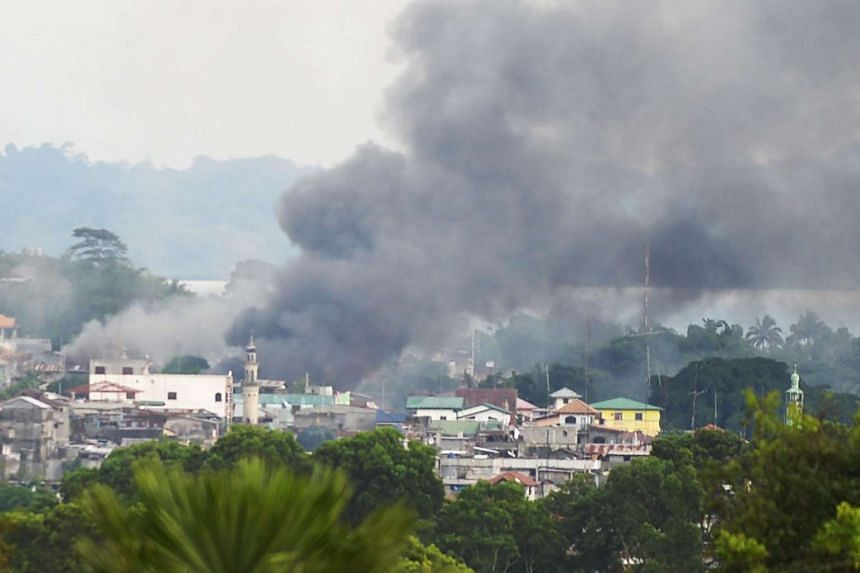 Smoke rises near a public market after military attack helicopters fired rockets on the positions of Muslim extremists in Marawi City.