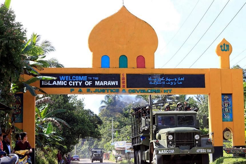 Government troops drive past a marker of Marawi city, southern Philippines on May 26.