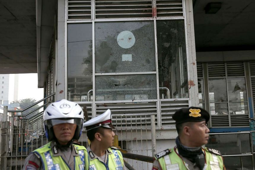 Policemen stand guard near a bus station damaged by bomb blast in Jakarta, Indonesia on May 25, 2017.