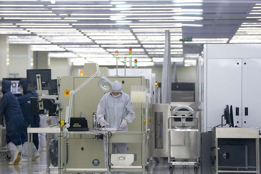 Employees at work in a United Test and Assembly Center (UTAC) Group semiconductor facility in Singapore.