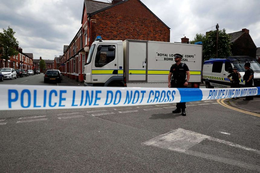 A bomb disposal unit and police officers wait behind cordon outside an address in Moss Side, Manchester, Britain, on May 27, 2017.