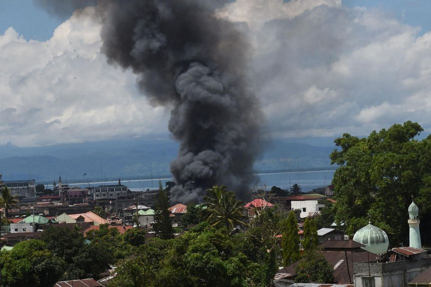 Black smoke billows from burning houses after government planes and helicopters bombed Islamic militants position in Marawi, in southern island of Mindanao on May 27, 2017.