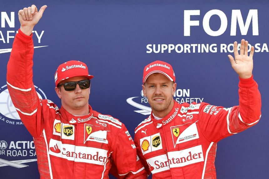 Ferrari's Finnish driver Kimi Raikkonen (left) celebrates after winning the pole position next to second placed Ferrari's German driver Sebastian Vettel.