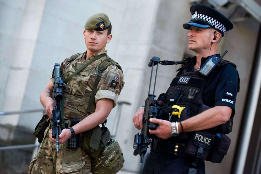 A British army soldier (left) and a police officer (right) secure an entrance to the Ministry of Defence in central London on May 25, 2017.