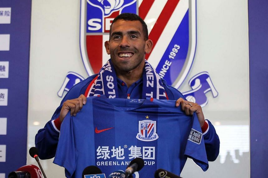 Argentine striker Carlos Tevez posing with a jersey of his new club Shanghai Shenhua, in January 2017.
