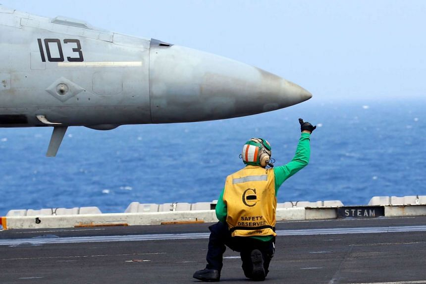 A flight deck crew member gives a hand signal to the pilot of a US Navy F18 fighter jet.