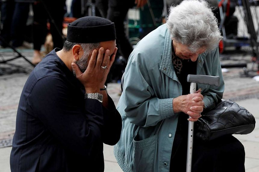 A Jewish woman named Renee Rachel Black (right) and a Muslim man named Sadiq Patel praying next to floral tributes in Albert Square in Manchester, on May 24, 2017.