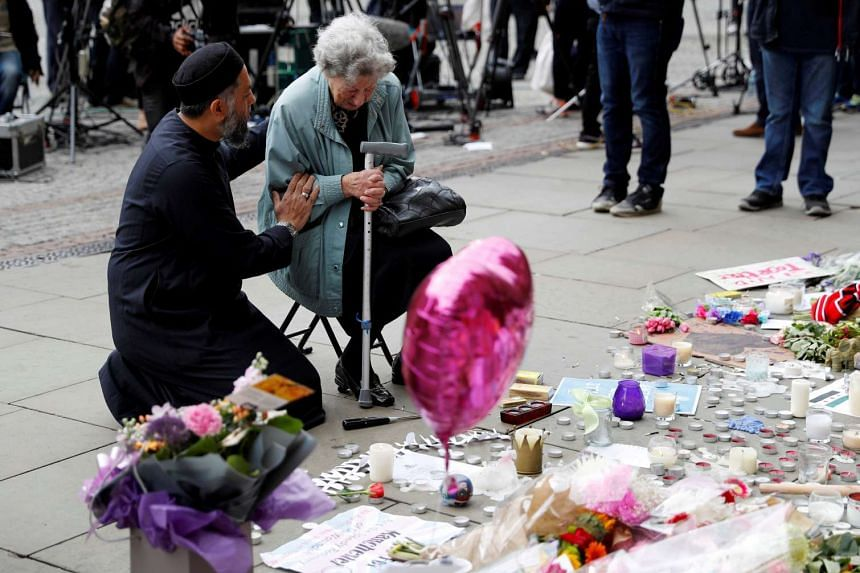 A Muslim man named Sadiq Patel comforting a Jewish woman named Renee Rachel Black next to floral tributes in Albert Square in Manchester, on May 24, 2017.