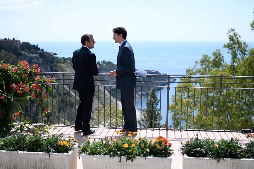 Macron (left) and Trudeau  talk as they attend the G-7 Summit in Taormina, Sicily.
