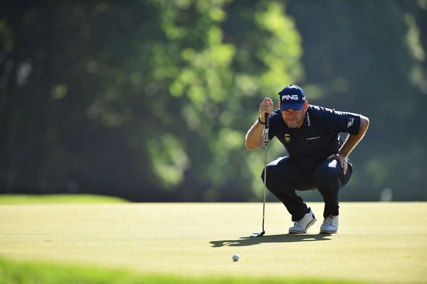 Westwood lines up his putt on the first green on the second day.