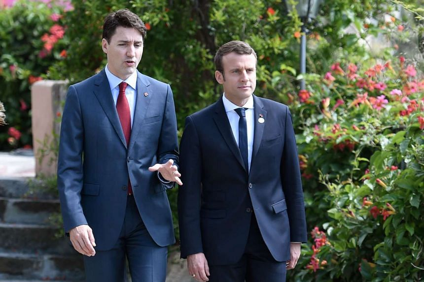 Macron (right) and Trudeau  talk as they attend the G-7 Summit in Taormina, Sicily.
