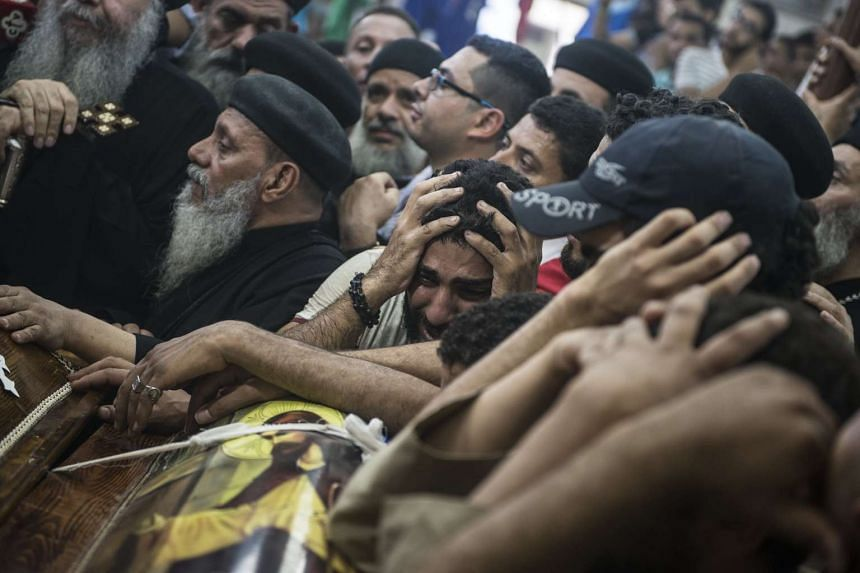 Relatives mourn over the coffins of victims of the attack on Christians, May 26, 2017.