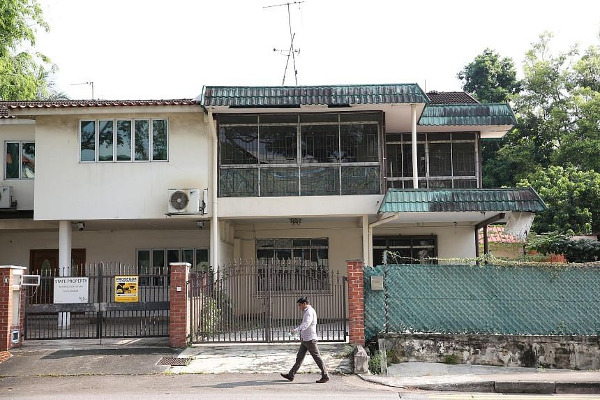 A passer-by in front of 33, Merpati Road, which has been taken over by SLA as its owners are no longer occupying it. Meanwhile, the remaining occupants of 27 and 29, Merpati Road are in the midst of packing up and moving out.