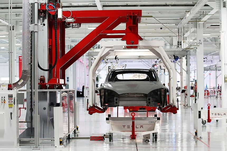 The body of a Tesla Model S is lifted by an automated crane at the Tesla factory in Fremont, California, in a 2011 file photograph.