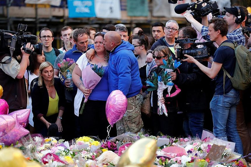 Above: Mrs Charlotte Campbell, whose 15-year-old daughter Olivia died in the Manchester attack, with Olivia's stepfather Paul Hodgson and other mourners at St Ann's Square. Right: Floral tributes left at St Ann's Square in memory of those who died in