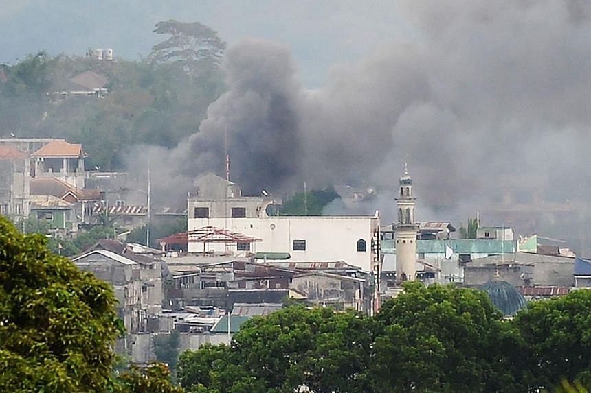 Residential areas in Marawi on fire after military helicopters fired rockets targeting Muslim extremists on Thursday. An army brigade has been sent to dislodge them, but they remained holed up in parts of the mainly Muslim city last night.