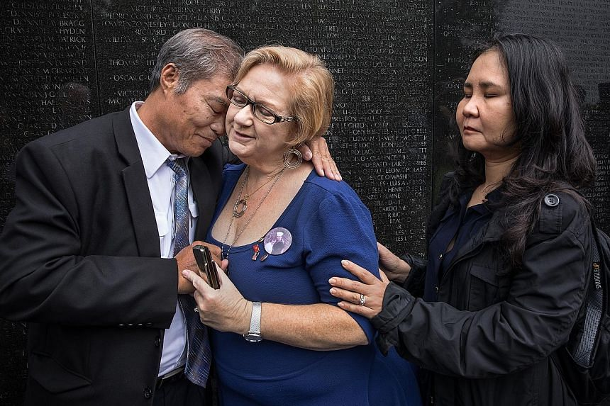 Mr Vu Ngoc Xiem with Ms Susan Mitchell-Mattera and Ms Nguyen Thi Hong Diem at the Vietnam Veterans Memorial in Washington on Thursday. The two women are children of people who died in the Vietnam war.