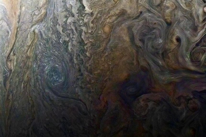 "Jupiter's south pole (far left) as seen by the Juno spaceship, and an enhanced-colour image (left) of a mysterious dark spot on Jupiter which is a Jovian ""galaxy"" of swirling storms."