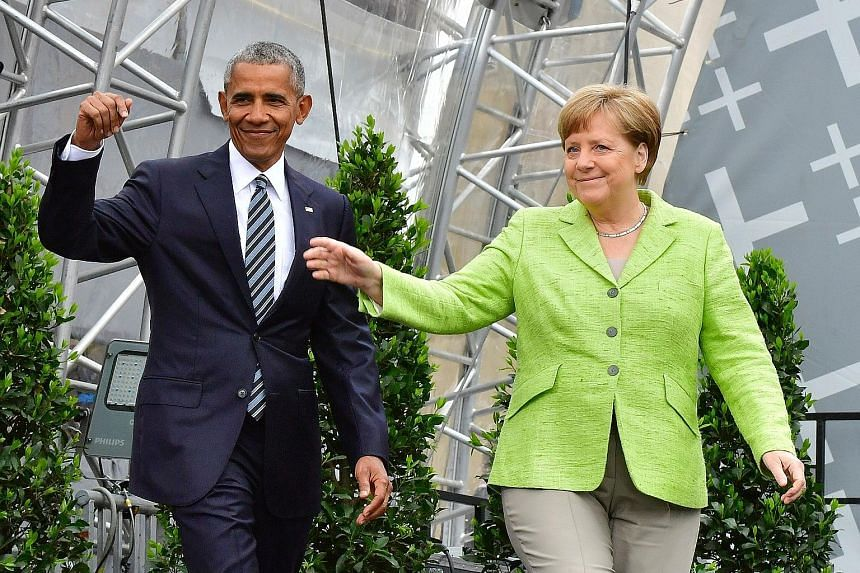 Former US president Barack Obama and German Chancellor Angela Merkel arriving on stage for a forum on democracy held at the Brandenburg Gate in Berlin yesterday. Mr Obama later spent 90 minutes talking about international and US issues without once m