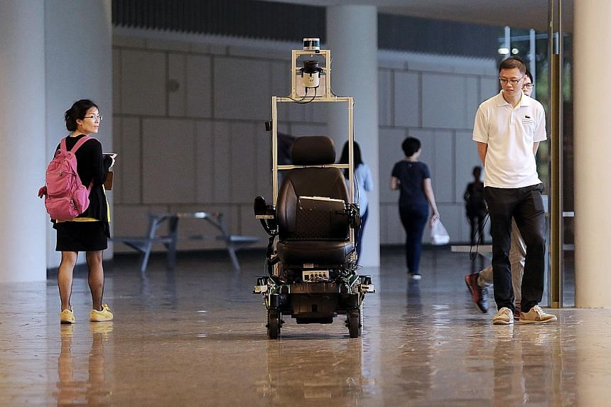 The self-driving wheelchair moving along a mapped-out route at the National University of Singapore. It was piloted at Changi General Hospital last September.