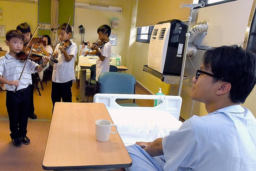 Little Heartstrings, made up of young musicians aged six to 14, playing the violin for a patient, Mr Khairi, as part of the MusicFest@SGH yesterday. The event, now in its fifth year, had more than 250 volunteer musicians taking music to the Singapore