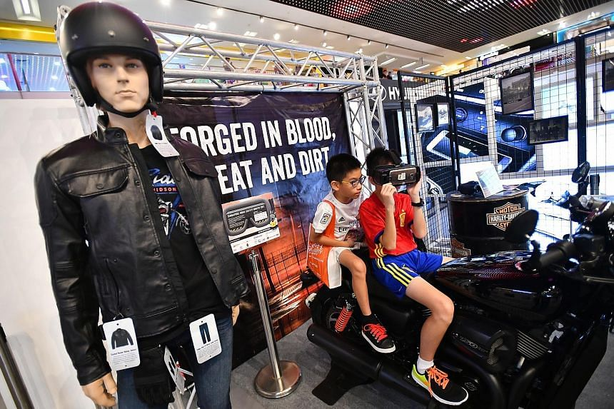 Jayden Koh, 11, trying out the virtual reality technology at the Road Sensibility booth for motorcyclists with his brother Joshua, nine, watching on, at the launch of the Singapore Road Safety Month yesterday. The initiative helps to guide motorcycli