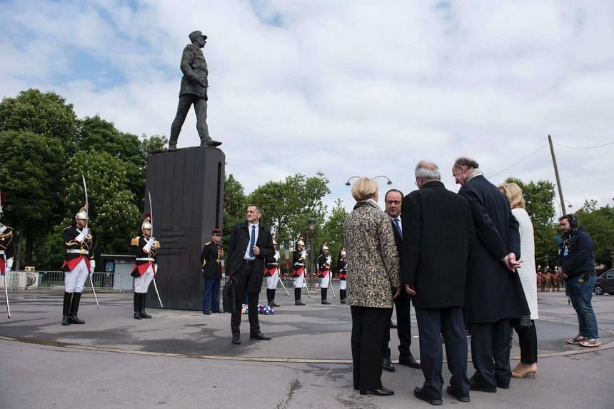 French President Francois Hollande (right) stands near a statue of Charles de Gaulle at a World War II ceremony in Paris.