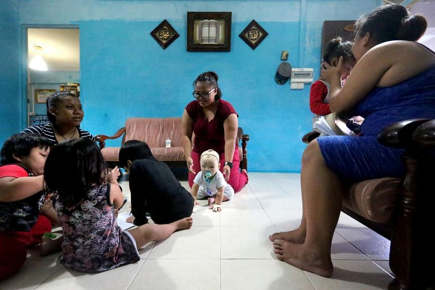 Ms Nurul Asyiqin Buang (centre), 20, and her family in their two-room rental flat in Tampines.