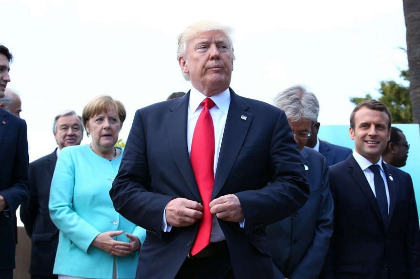 Trump reacts after a family photo at the G-7 Summit expanded session in Taormina, Sicily.