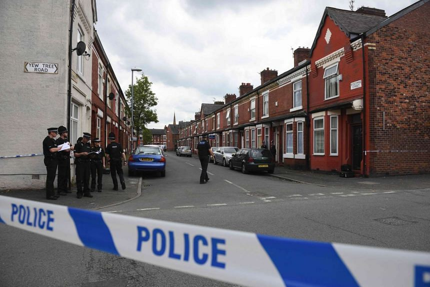 Police officers work outside the entrance to a property they entered in the Moss Side area of Manchester on May 27, 2017 during an operation.