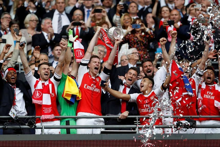 Per Mertesacker and Laurent Koscielny celebrate with the trophy after winning the FA Cup final.