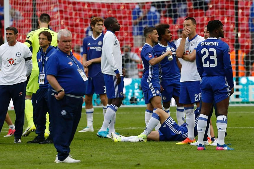 Chelsea staff and players - including John Terry (second right) - react on the pitch after their defeat.