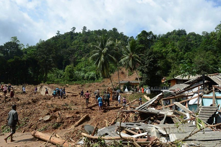 Military rescue workers and villagers searching for survivors at the site of a landslide, in Athweltota village in Kalutara, Sri Lanka, on May 28, 2017.