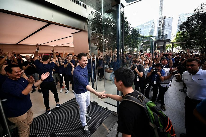 Mr Xiang Jiaxin being welcomed as Apple Orchard Road's first customer yesterday. He had queued from 8pm last Friday night.