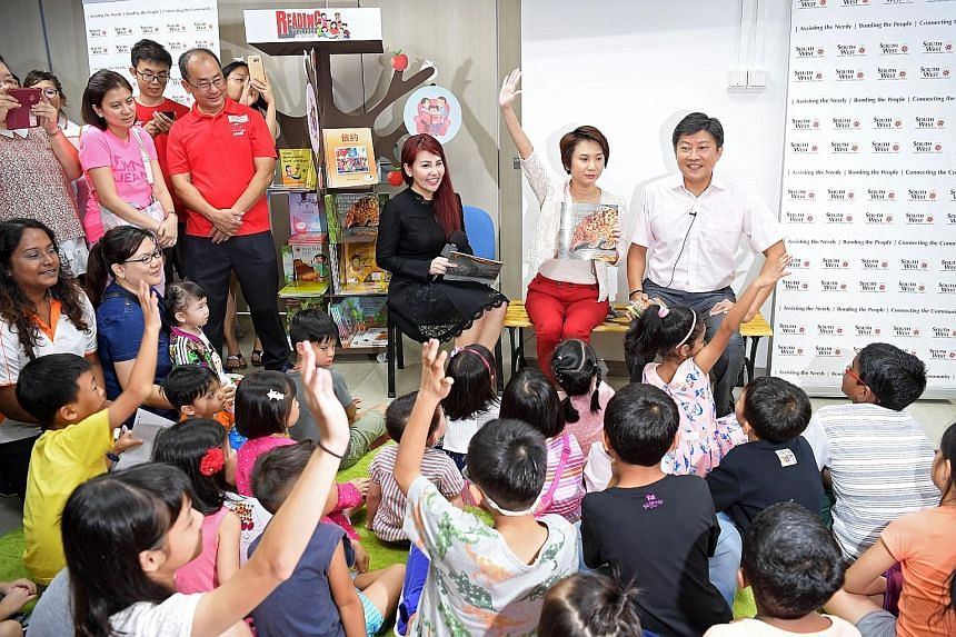 Education Minister (Schools) Ng Chee Meng with (seated from left) South West CDC Family and Active Ageing Functional Committee vice-chairman Jenny Wee and South West District Mayor Low Yen Ling entertaining children at a story-telling session at yest