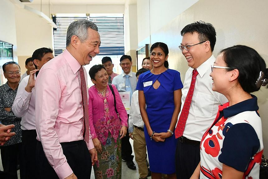 Prime Minister Lee Hsien Loong with new citizens - Singapore Airlines air stewardess Kavitha Sathekoma, 28; IT director Donny Liu, 41, and his wife Tina Chen, 35, a finance manager - at the end of the Ang Mo Kio GRC-Sengkang West SMC Citizenship Cere