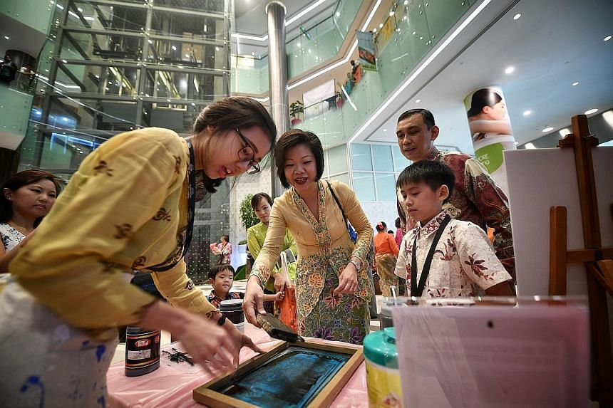 Ms Sim Ann (centre), Senior Minister of State for Culture, Community and Youth, and Trade and Industry, trying out silkscreen printing on a tote bag at the atrium of Claymore Connect mall in Orchard Road yesterday. The activity was part of the Perana
