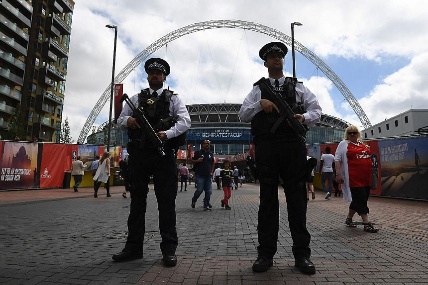 Armed police standing guard outside Wembley Stadium in London yesterday. Elsewhere in the capital, police patrols were visible at underground and rail stations and on the streets, especially in tourist areas.