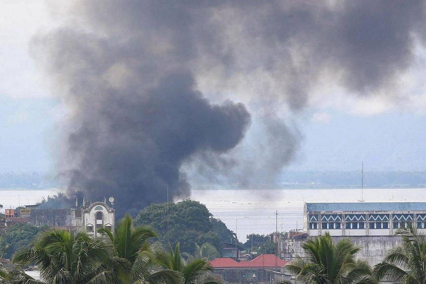 Smoke billows behind a mosque in a residential neighbourhood in Marawi City due to fighting between government soldiers and the Maute militant group, in southern Philippines on May 28, 2017.