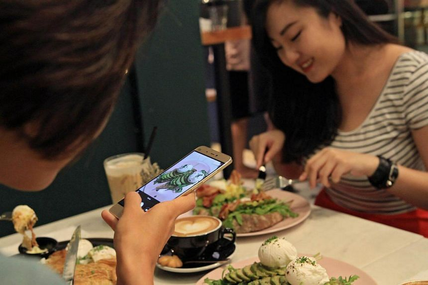Posed picture of Ms Salima Nadira, 27, taking a picture of her meal comprising of avocado toast.