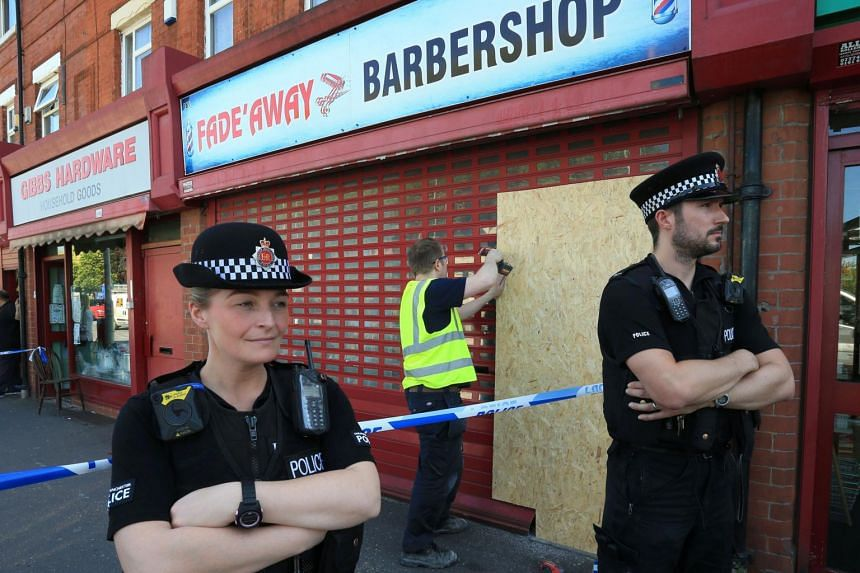 Police stand on duty as a worker boards up a cut-away section of shutter at the Fade Away barber shop in Manchester on May 26, 2017.