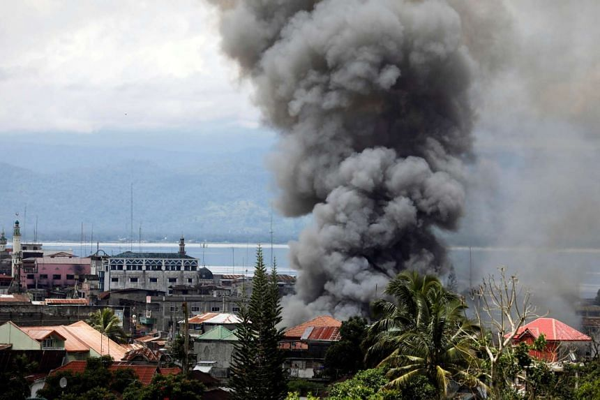 Smoke rising in the residential neighbourhood of Marawi city, as fighting raged on between government soldiers and the Maute militant group, on the first day of the holy Muslim month of Ramadan yesterday. About four-fifths of Marawi's population of a