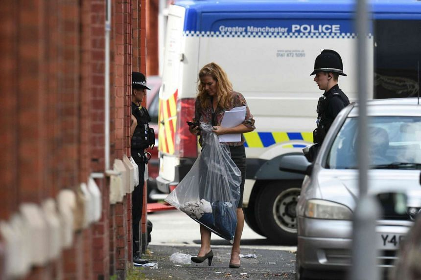 Police officers carry a plastic evidence bag containing items outside the entrance of a property they entered in the Moss Side area of Manchester on May 27, 2017 during an operation.
