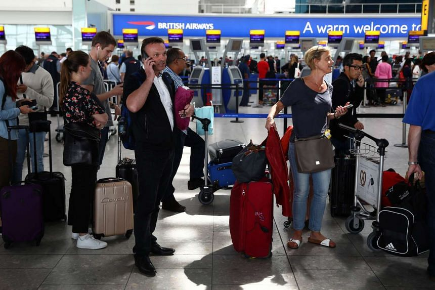 People wait with their luggage at the British Airways check in desks at Heathrow Terminal 5 in London, Britain on May 28, 2017.