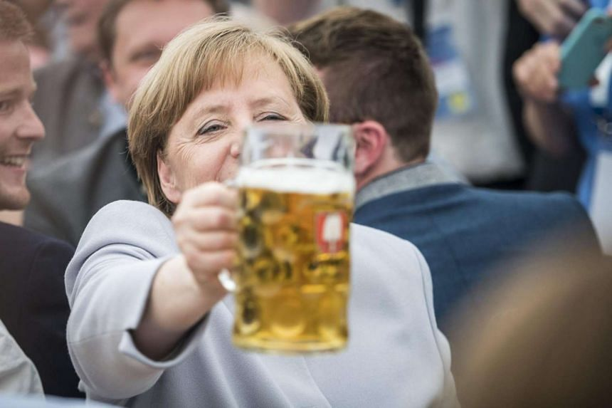 German Chancellor Angela Merkel toasts with a beer during the election campaign event at the 46th Truderinger Festwoche festival week in Munich.